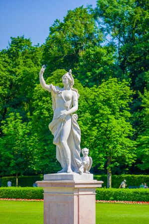 nymphenburg palace: Nymphenburg, Germany - July 30, 2015: Sculpture of woman, beautiful sunny day, green grass and bushes in palace gardens.