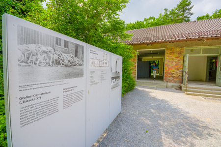 sachsenhausen: Dachau, Germany - July 30, 2015: Outside view of krematorium building with information sign visible to the side.