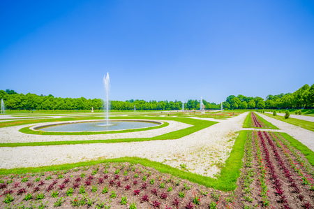 gravel roads: Schleissheim, Germany - July 30, 2015: Royal garden of palace property with incredible organized green bushes and gravel roads, water fountain, majestic design, beautiful blue sky.