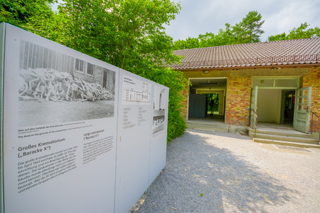 documented: Dachau, Germany - July 30, 2015: Outside view of krematorium building with information sign visible to the side.