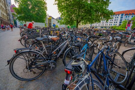 parking station: Munich, Germany - July 30, 2015: Pubic bicycle parking station with countless bikes standing lined up.