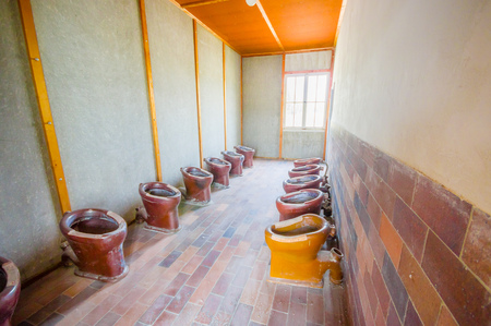 german fascist: Dachau, Germany - July 30, 2015: Inside bathroom are with many toilets installed in a row for all prisoners to use at concentration camp. Editorial