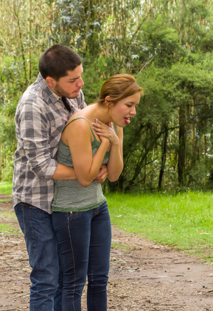 choking: Young woman choking with man standing behind performing heimlich maneuver, park environment and casual clothes.