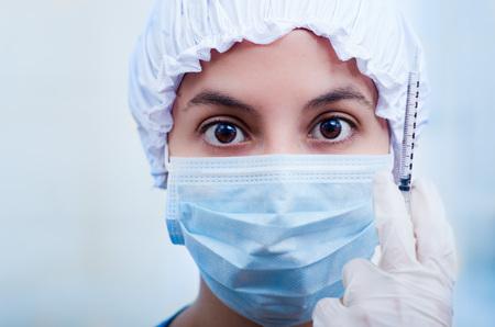 bouffant: Closeup headshot nurse wearing bouffant cap and facial mask holding up syringe needle for camera. Stock Photo