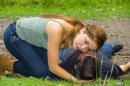 Young man lying down with medical emergency, woman sitting by his side checking for breath, outdoors environment. Stock fotó