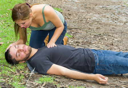 Young man lying down with medical emergency, young woman sitting by his side performing light treatment, outdoors environment.