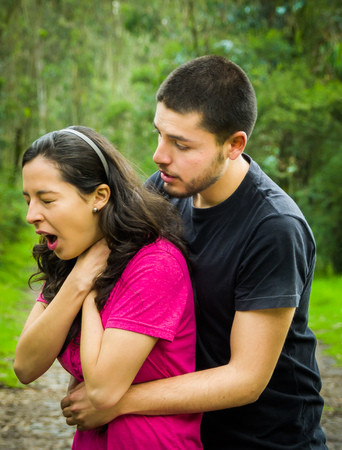 Young woman choking with man standing behind performing heimlich maneuver, park environment and casual clothes.