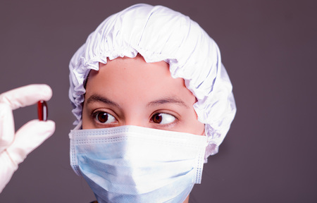 Nurse wearing bouffant cap and facial mask holding up brown pill capsule for camera, grey background.