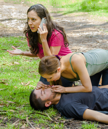Young man lying down with medical emergency, two young women performing cpr breathing aid, outdoors environment. Stock fotó