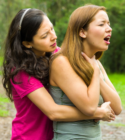 choking: Young woman choking with lady standing behind performing heimlich maneuver, park environment and casual clothes.