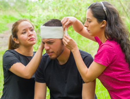 Young man with head injury receiving treatment and bandage around skull from two women, outdoors environment.