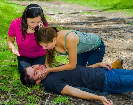 emergencia medica: El hombre joven que se acuesta con urgencia médica, dos mujeres jóvenes la realización de los primeros auxilios, el medio ambiente al aire libre.