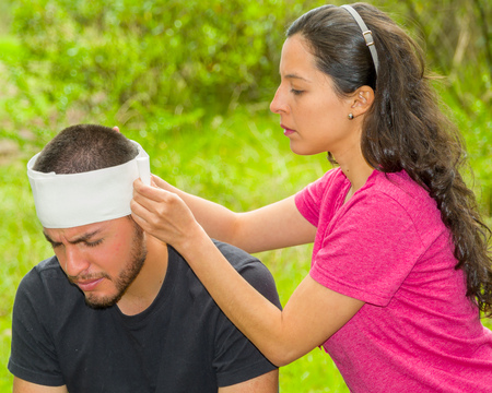Young man with head injury receiving treatment and bandage around skull from woman, outdoors environment.