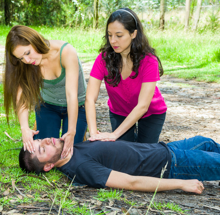 Young man lying down with medical emergency, two young women performing first aid, outdoors environment.
