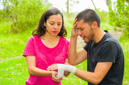 Young man with injured wrist sitting and getting bandage compression wrap from female, outdoors environment.