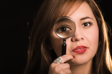 facing right: Young woman facing camera holding magnifying glass over right eye creating enhanced effect, black background.