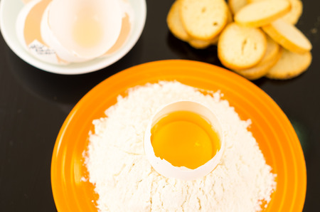 cracked egg: Strong yellow colored plate with flour crater containing cracked egg shot from above side angle. Stock Photo