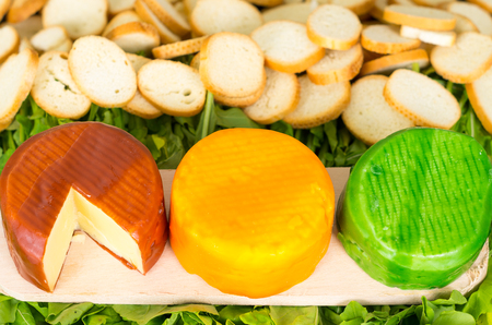 packed: Very nice delicate presentation of three different flavored cheeses packed in brown. yellow and green placed on wooden surface with plants background.