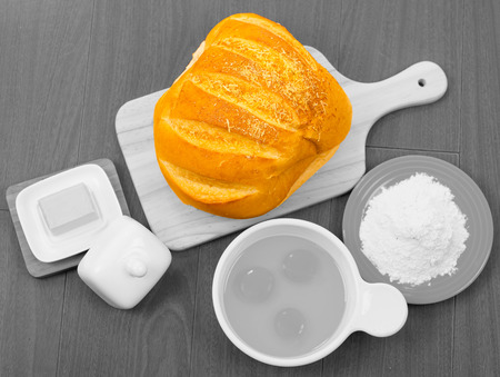 beautifully: Beautifully colored loaf of bread stands out as eggs, cheese and flour are in black white .