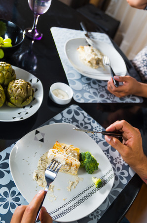 cooked pepper ball: Crepe covered in white sauce lying on plate with broccoli pieces, man eating as seen from above, classy table setting. Stock Photo