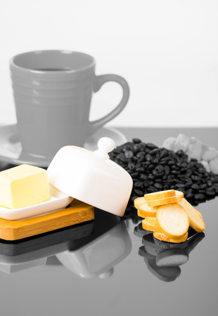 coffe beans: Grey coffe cup on shiny surface sourrounded by cheese, small toasts and coffee beans.