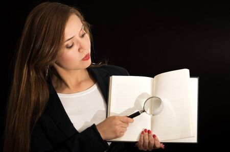 facing to camera: Young brunette woman facing camera holding up open book and magnifying glass above pages.