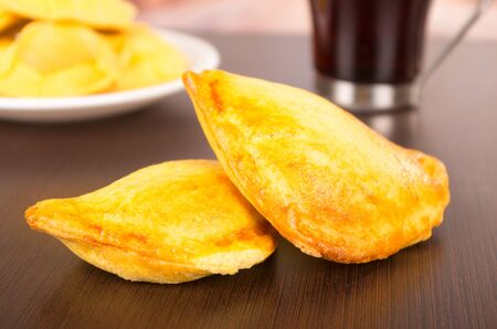 golde: Fried filled empanadas on a table, behind delicious coffee on a cup Stock Photo