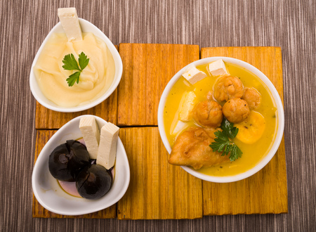 ecuadorian: Traditional fanesca serving sitting on wooden surface with accessories next to it such as molo mashed potatoes and fig dessert.