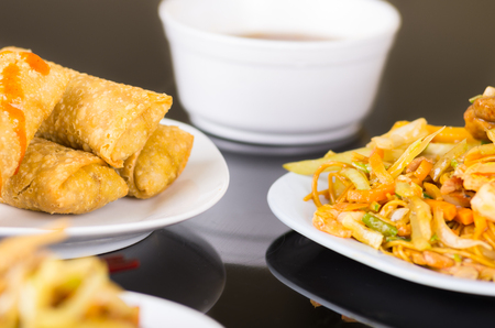 chinesse: Chinesse food, spring rolls and noodles with vegeatbles served on a white dishes, wooden table