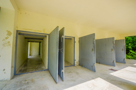 sachsenhausen: Dachau, Germany - July 30, 2015: Heavy metal doors leading into the krematorium building at concentration camp.