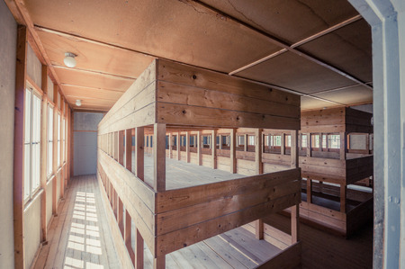 Dachau, Germany - July 30, 2015: Inside sleeping quarters with wooden bunk beds showing prisoners terrible living conditions. Editorial