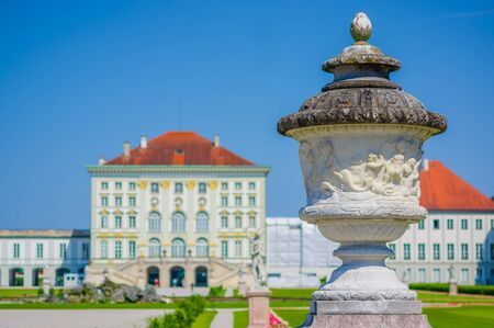 nymphenburg palace: Nymphenburg, Germany - July 30, 2015: Palace building shot from artistic angle with sculpture visible up close, beautiful blue sky and green grass contrasts.