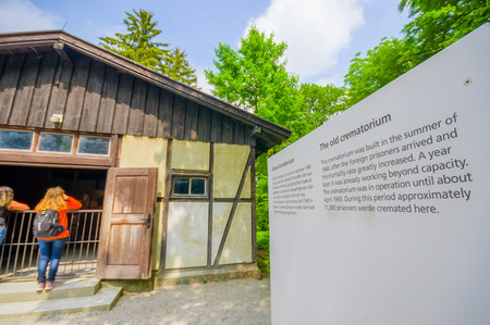 sachsenhausen: Dachau, Germany - July 30, 2015: Outside view of old krematorium building with information sign visible to the side.