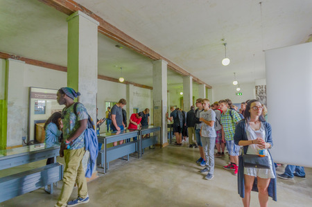 Dachau, Germany - July 30, 2015: Crowd of people looking inside museum buildings concentration camp.