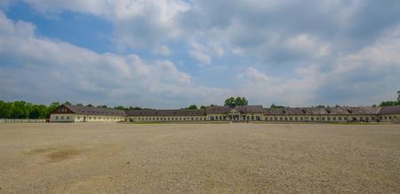 sachsenhausen: Dachau, Germany - July 30, 2015: Large open gravel square inside concentration camp, barracks and administration buildings sorrounding. Editorial