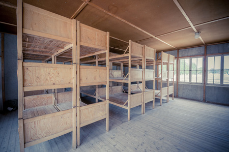 prisoners: Dachau, Germany - July 30, 2015: Inside sleeping quarters with wooden bunk beds showing prisoners terrible living conditions. Editorial