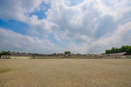 Dachau, Germany - July 30, 2015: Large open gravel square inside concentration camp, barracks and administration buildings sorrounding. Editorial