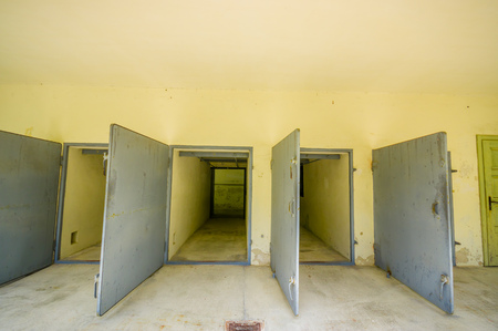 slave labor: Dachau, Germany - July 30, 2015: Heavy metal doors leading into the krematorium building at concentration camp.