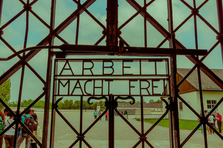 german fascist: Dachau, Germany - July 30, 2015: Metal sign at entrance gate to concentration camp which reads Arbeit Macht Frei.