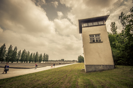 Dachau, Germany - July 30, 2015: Tall cement guard towers as seen from ground inside concentration camp, overlooking prisoners yard. Editorial