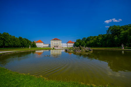 nymphenburg palace: Nymphenburg, Germany - July 30, 2015: Beautiful palace as seen from distance across lake, beautiful scenerey and green gardens sorrouding.