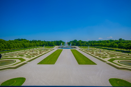 gravel roads: Schleissheim, Germany - July 30, 2015: Royal garden of palace property with incredible organized green bushes and gravel roads, majestic design, beautiful blue sky. Editorial