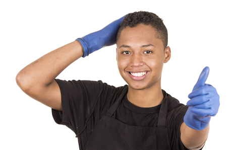 facing right: Closeup hispanic young man wearing blue cleaning gloves facing camera with right arm raised holding head and other hand giving thumbs up.