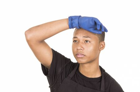 facing right: Hispanic young man wearing blue cleaning gloves facing camera with right arm raised. Stock Photo