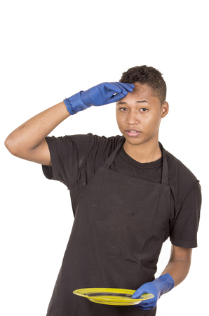 looking towards camera: Hispanic young man wearing blue cleaning gloves holding green plate looking tired facial expression towards camera.