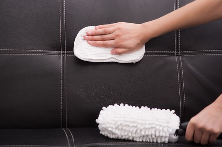 hand rubbing: White fabric brush from steam cleaning machine being used on black leather couch, hand rubbing sofa with cloth. Stock Photo