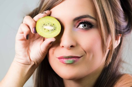 green lipstick: Headshot brunette, dark mystique look and green lipstick, covering one eye with open kiwi, looking into camera,