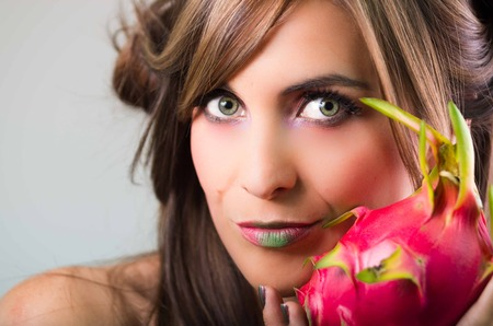 mystique: Headshot brunette, dark mystique look and green lipstick, holding up pink pitaya fruit, looking into camera.