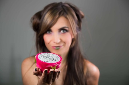 green lipstick: Headshot brunette, dark mystique look and green lipstick, holding up two open halfs of pink pitaya fruit with both hands facing camera.