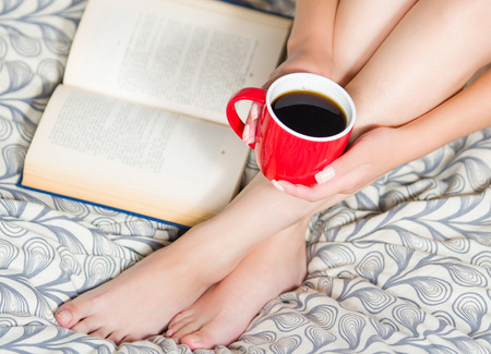 legs open: Woman sitting on bed, only legs visible, holding red coffee cup and open book lying next to feet.